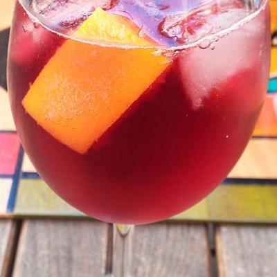 Weinglas mit einem rötlichen Getränk in dem Früchte und Eiswürfel schwimmen